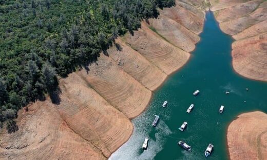Houseboats are dwarfed by the steep banks of Lake Oroville