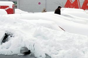 A man walks between cars covered with snow in Podgorica.