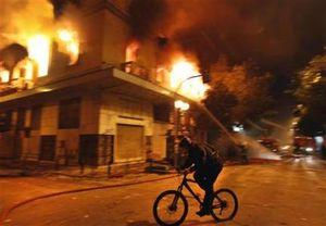cyclist rides past a burning building