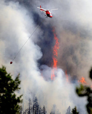 A firefighting helicopter flies above the fire near Bison Drive on Tuesday west of Boulder.