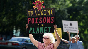 Protestors hold signs against fracking